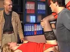 Two men share young office girl in red on table